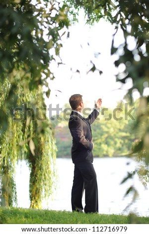 Young businessman in a sunny park.