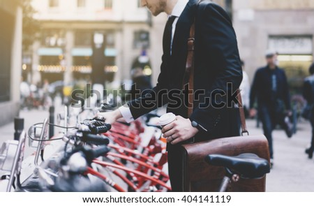 Young businessman in black modern suit with coffee cup and going to work by city bicycle on urban street in the morning, environment concept - stock photo
