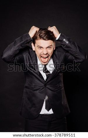 young businessman in black suit tearing hair out in anger and looking at camera. emotions and people concept. image on a black studio background. - stock photo
