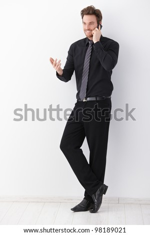 Young businessman in black talking on mobile phone, gesturing, smiling. - stock photo