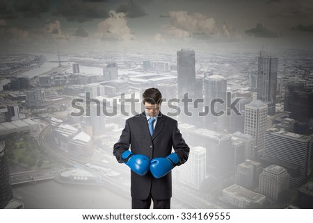Young businessman in blue boxing gloves on city background