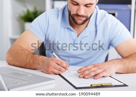 Young businessman in blue polo shirt signs a contract on white table - stock photo