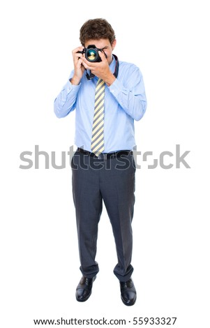 young businessman in blue shirt and necktie takes photo with dslr camera, studio shoot isolated on white background - stock photo
