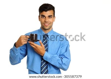 Young businessman in blue shirt holds cup of coffee, right you can write some text