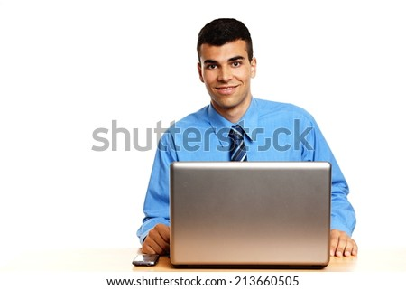 Young businessman in blue shirt sits at the laptop, left you can write some text - stock photo