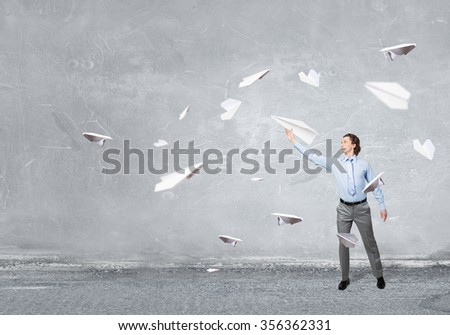 Young businessman in concrete room with paper plane in hand