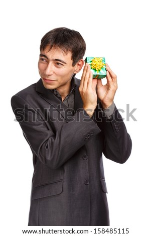 Young businessman in dark grey suit standing isolated on white background holding unexpected gift