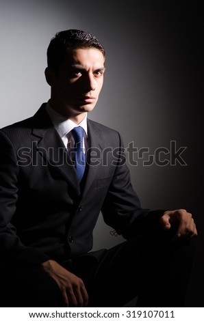 Young businessman in dark studio - stock photo