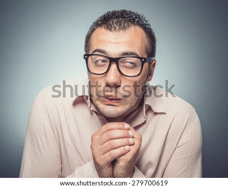 Young businessman in fear. Close up of a funny afraid formal man over gray background