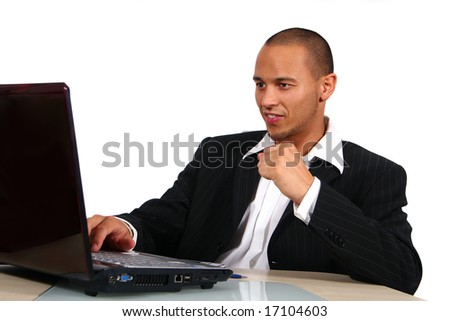 Young Businessman In Front Of Laptop A young businessman sitting by desk at office working on the laptop with a table out of glass and wood. - stock photo