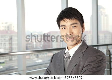 Young Businessman in front of window - stock photo