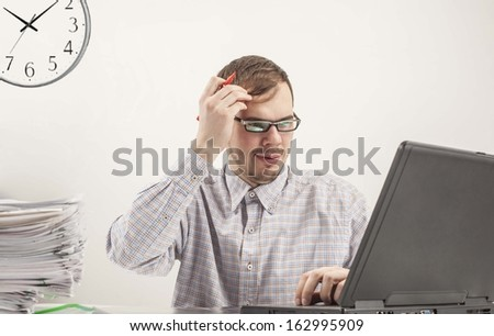 Young businessman in glasses hardworking and  looking at screen black laptop at desk in his office on background gray wall with clock  - stock photo
