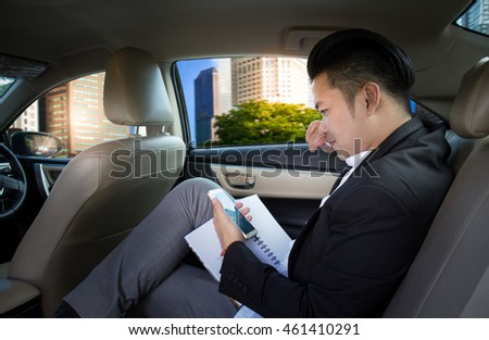 Young businessman in gray suit sitting in a new car and holding the mobile phone