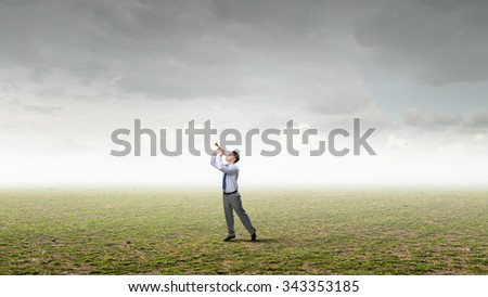 Young businessman in green field playing pipe