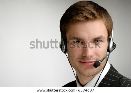 young businessman in headphones speaks on  microphone on  grey background - stock photo