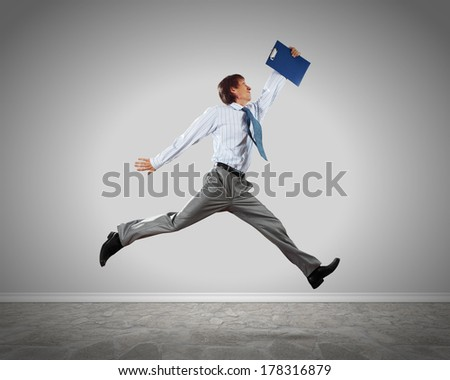Young businessman in jump against blank background - stock photo