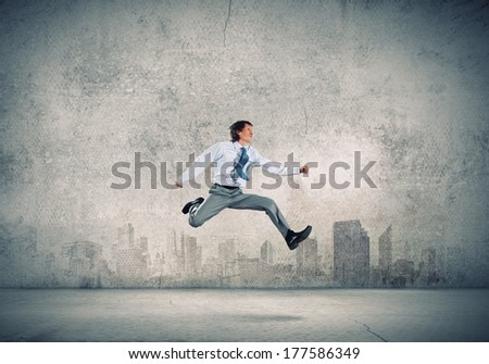 Young businessman in jump against city background