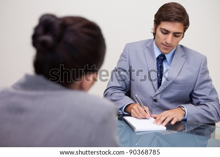 Young businessman in meeting taking notes