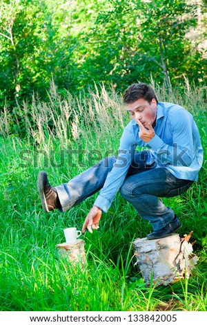Young businessman in nature doing acrobatic poses