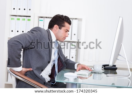 Young Businessman In Office At Desk Suffering From Back Pain