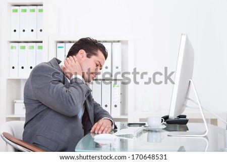 Young Businessman In Office At Desk Suffering From Neck Pain - stock photo