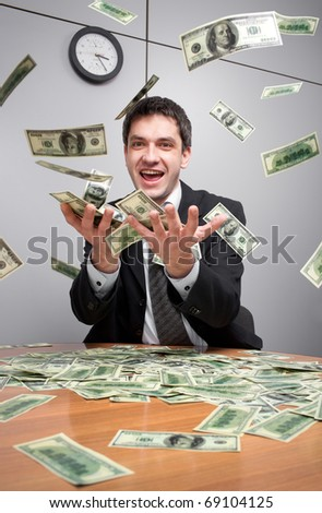 Young businessman in office catch a lot of money in the air - stock photo