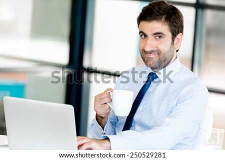 Young businessman in office holding a mug