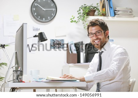 Young businessman in office looking at camera. Businessman with rimmed glasses working. - stock photo