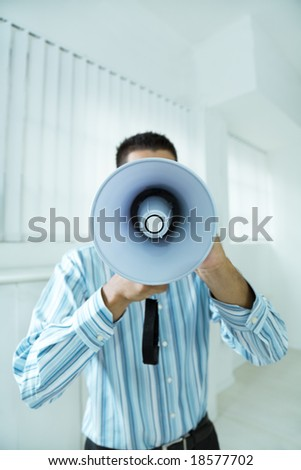 young businessman in office screaming on the megaphone