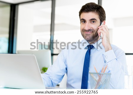 Young businessman in office talking over mobile