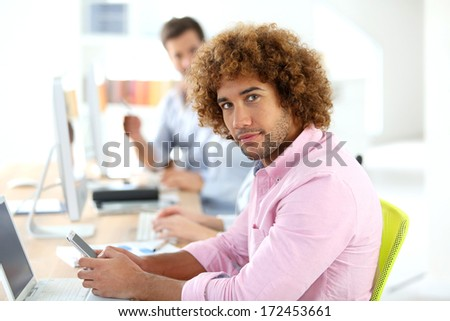 Young businessman in office using smartphone