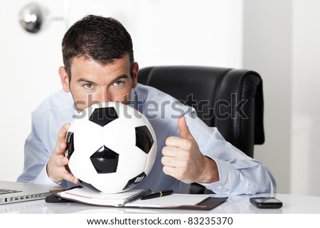 young businessman in office with computer and ball - stock photo