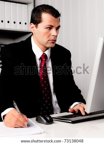 Young Businessman in office with computer in office - stock photo