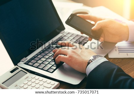 young businessman in office with smartphone tablet at workplace