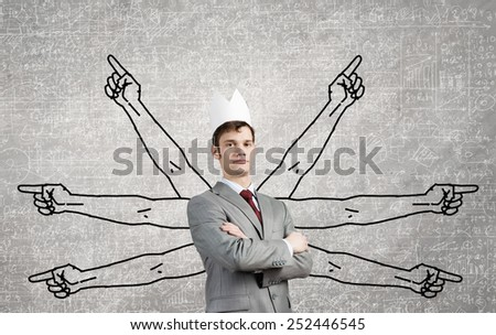 Young businessman in paper crown and many hands around him - stock photo