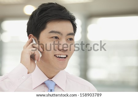 Young businessman in pink button down shirt on the phone - stock photo