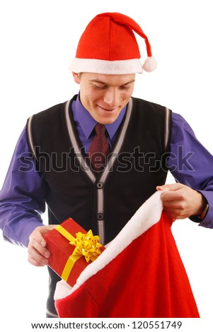 Young businessman in santa hat offering a gift to you - stock photo