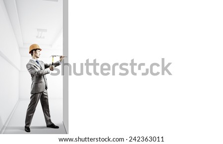 Young businessman in suit and hardhat hammering nail in wall - stock photo