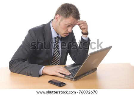 Young businessman in suit and tie sits at his desk, he wonders, looking in his notebook PC. Isolated against a white background