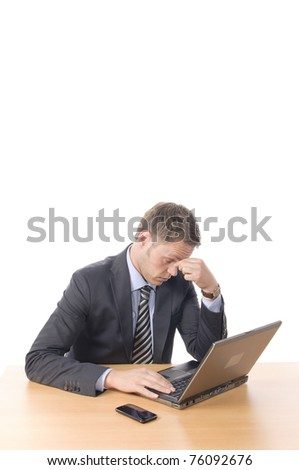 Young businessman in suit and tie sits at his desk, he wonders, looking in his notebook PC. Isolated against a white background - stock photo