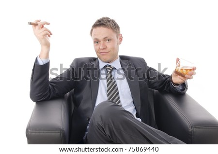 Young businessman in suit and tie, sitting at a desk and enjoy a good cigar from his humidor. Isolated against a white background - stock photo