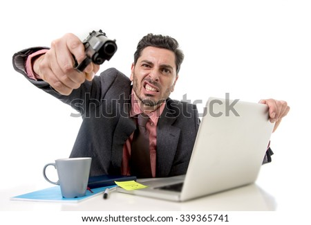 young businessman in suit and tie sitting at office desk working on computer laptop pointing gun looking angry and crazy in business stress and overwork concept - stock photo