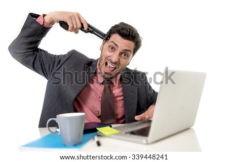 young businessman in suit and tie sitting at office desk working on computer laptop pointing gun on his tempo in suicide gesture looking sad and depressed in business stress and overwork concept - stock photo