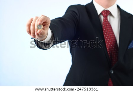 Young businessman in suit holding one Euro coin