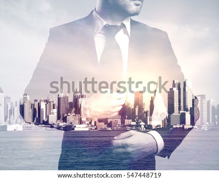 Young businessman in suit on abstract city background. Double exposure