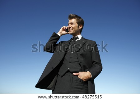 Young businessman in suit on the phone outdoors - stock photo