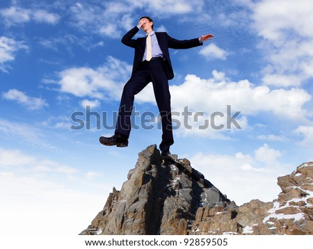Young businessman in suit ready to take risky steps - stock photo