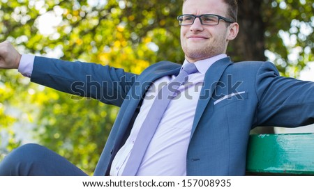 Young businessman in suit resting on bench in park.