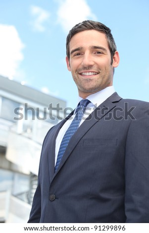 Young businessman in suit stood outside building - stock photo