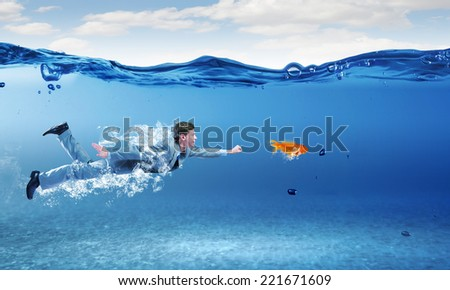 Young businessman in suit swimming under water - stock photo